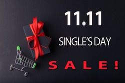 11.11 Single day sale. Red gift with red ribbon on black color background and small cart on black color background with white 11.11 single's day sale text