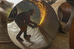 Skilled metal worker grinding weld joints producing golden sparks inside large iron pipe wearing protective safety gear in  industrial weld shop.