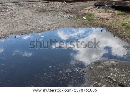 Sky reflected in a puddle of water on pavement  #1378761086