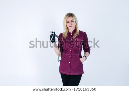 Slender young blonde girl master of manicure in black mask A girl with long hair in a pink uniform, a manicure master in a protective black mask from the covid virus with tools for processing nails Zdjęcia stock ©