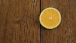 Slice of orange fruit, also known as lime orange, very well known in Brazil, very sweet fruit on wooden background in copy space