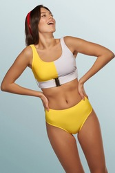 Slim lady is wearing two-piece swimsuit composed of gray and yellow bra with metal buckle and yellow high-waisted panties. Smiling girl with red headband is posing on the blue background.