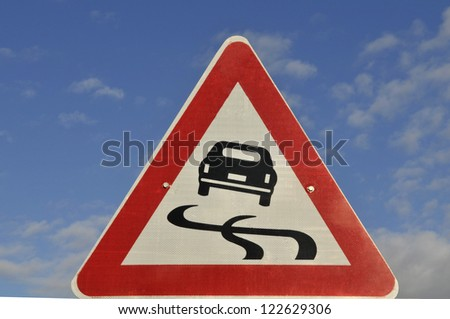 'slippery road' sign, against  blue sky.