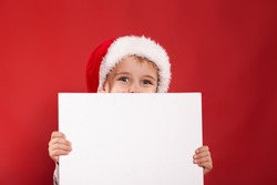 small boy with white table  on a red background in studio Concept for Celebrate, Christmas, New Year, sales and Family