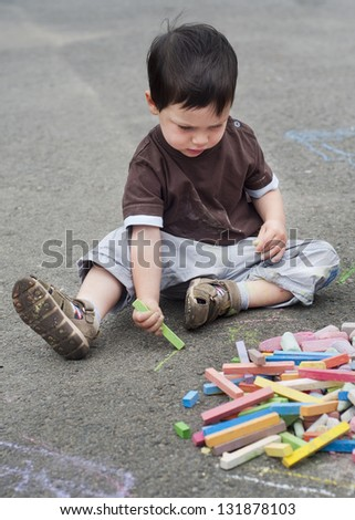 Small child, boy or girl, drawing on a asphalt road or pavement with a chalk.