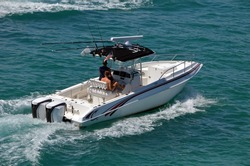 Small open white fishing boat with center console cruising the Florida Intra-Coastal Waterway off Miami Beach.