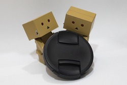 small robots holding the lens cover