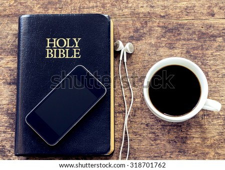 smartphone over the holy bible with black coffee cup on wooden background, vintage color