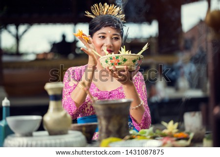 Smiling Balinese woman in a pink dress making flower offerings to the Gods at a Hindu temple