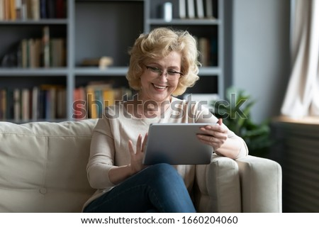 Smiling middle-aged Caucasian woman sit on couch in living room browsing wireless Internet on tablet, happy modern senior female relax on sofa at home using pad device, elderly technology concept