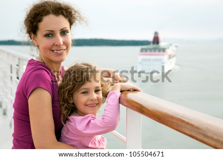 smiling mother and daughter traveling on big cruise ship, other ship in sea