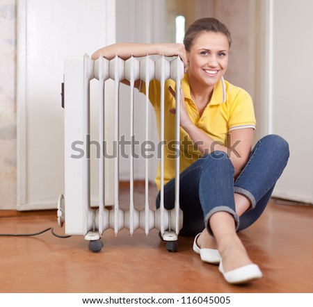smiling woman  near warm radiator  in home - stock photo