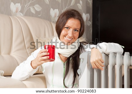 smiling woman   near warm radiator  in home