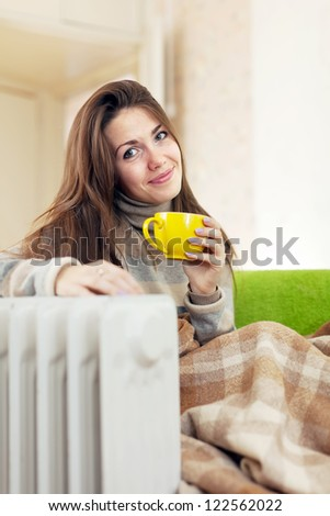 smiling woman  with yellow cup near oil heater