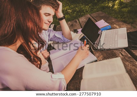 Smiling Young students couple sitting on a bench learning preparing for an exam in a city park.Students using tablet and laptop.Technology.Park.Preparing for Exam