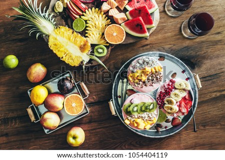 3 smoothie bowls with colorful tropical fruits on serving tray, top view from above. Summer healthy diet, vegan breakfast.