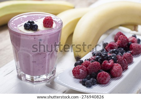 Smoothies of frozen raspberries, blueberries and banana with yogurt. Blueberries and raspberries on a white plate and a banana  on a wooden table.