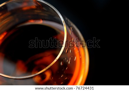 snifter of  brandy in  elegant  glass.  black background