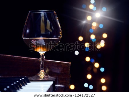 snifter with  brandy on a piano