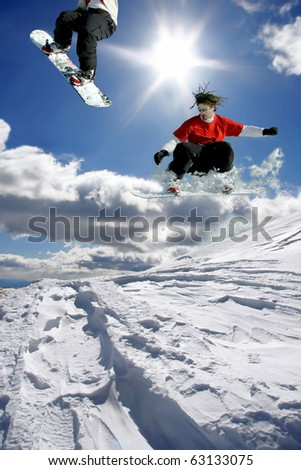 snowboarders jumping against blue sky