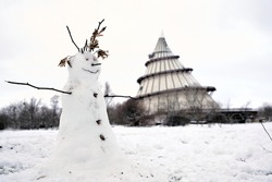 Snowman on a meadow in a Park in Magdeburg in Winter. In the background the millennium tower.