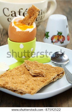 Soft-boiled egg, whole grain bread on the background of a coffee cup.