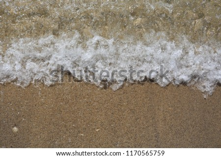 Soft wave of turquoise sea water on the sandy beach. Close-up and directly above photographed  #1170565759