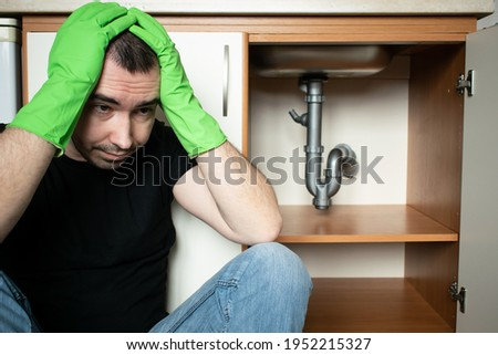 Solving Common Household Drain Problems, symptoms Solutions blockage plumbing kitchen sink pipe unclog male man sit tired Foto stock ©