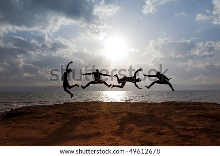 "...some guys with Dead-Sea-mud on their skin, are performing a funny jumping scene in front of the dead sea in jordan. ""Over the sea, some Miles beyond the mountains is Jerusalem"". - stock photo"