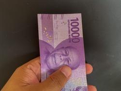 Someone hand holding Indonesian money, Rupiah,  10.000 bill over dark background