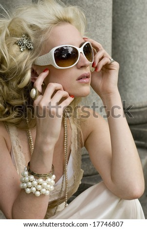 20-something female with red nail polish, white sunglasses and white dress