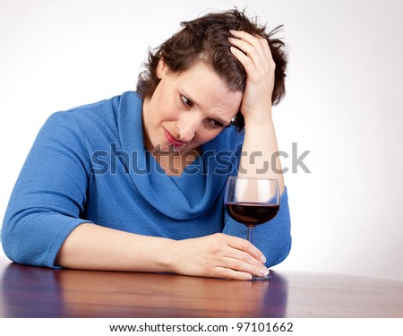 40 something woman staring at a glass of wine looking very upset