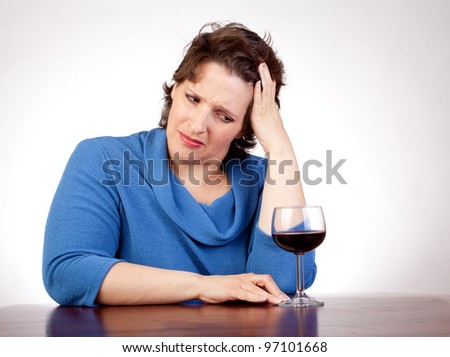 40 something woman staring at a glass of wine looking very upset - stock photo