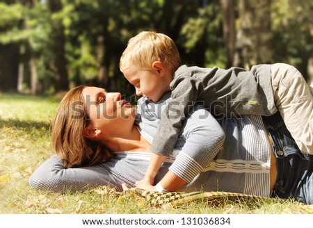 Son and mother tender hugs at the sunny day in park