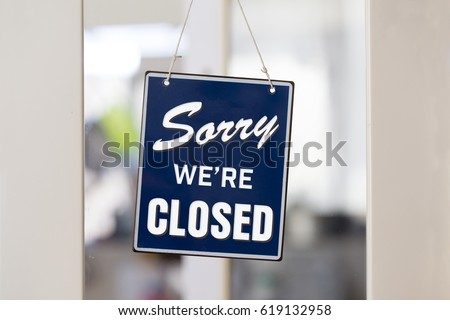 """ Sorry we're closed "" sign in blue and white, on shop glass door with white panels. #619132958"