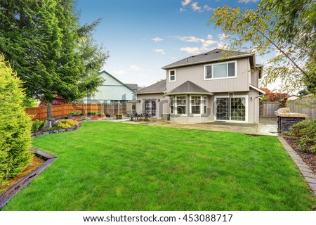 Spacious backyard garden of large beige house with green lawn and Cozy patio area.  #453088717