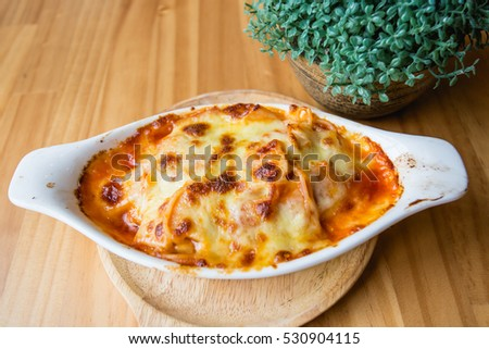 Spaghetti baked cheese on a wooden table.