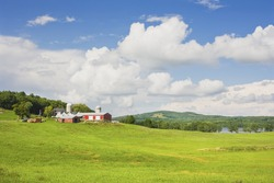 Spring farm and hay field with blue sky and clouds in maine.