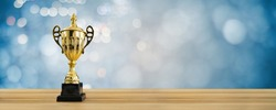 1st champion award, the best prize and winner concept, championship cup or winner trophy on wood table with soft blue and bokeh background