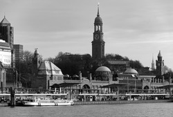 """""""St Pauli Landungsbruecken"""" and """"St. Michael's Church"""" at the Port of Hansestadt Hamburg Germany are famous landmarks, monuments and tourist attractions in the harbour cruise mooring, black and white"""