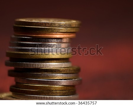 stack of coins against read background, closeup with shallow DOF