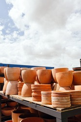 Stacked clay pots at sale in a garden center with blue sky in the background during spring
