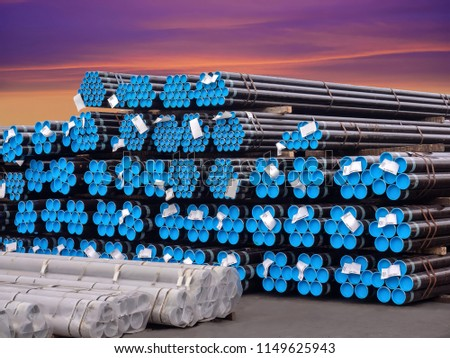 Stacking steel pipe in bundles at industrial yard for exporting.
