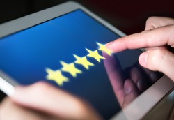 5 star rating or review in survey, poll, questionnaire or customer satisfaction research. Happy man giving positive feedback with tablet. Successful business with good reputation. Good experience.