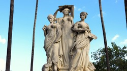 3 statues of women representing the arts as muses with palm trees in the background