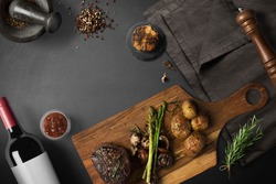 Steak with baked potatoes, asparagus, on wooden board, with wine and spices, top view with copy space