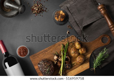 Steak with baked potatoes, asparagus, on wooden board, with wine and spices, top view with copy space Stock photo ©