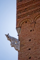 stone sculpture depicting a she-wolf on the facade of a historic building in red bricks