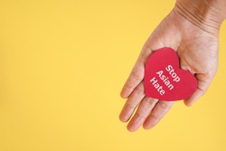 Stop Asian Hate , white message, on red heart paper in hand with yellow background and copy space , anti racist ,hate crimes against Asians concept