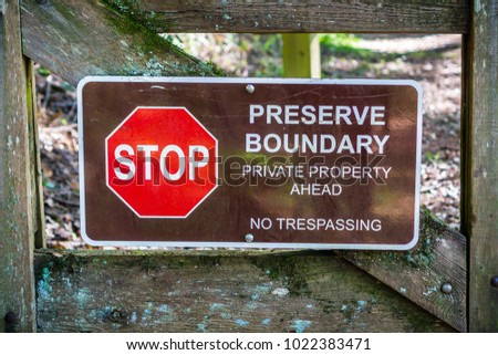 """""""Stop; Preserve Boundary; Private Boundary Ahead; No trespassing"""" sign posted on a wooden gate #1022383471"""